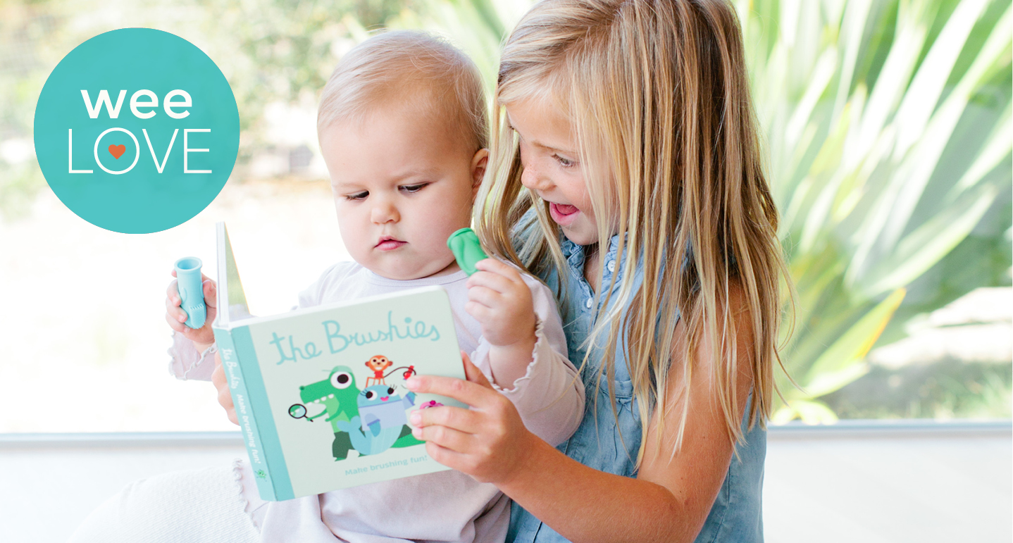 Girl reads Brushies book to baby while baby holds toothbrush.