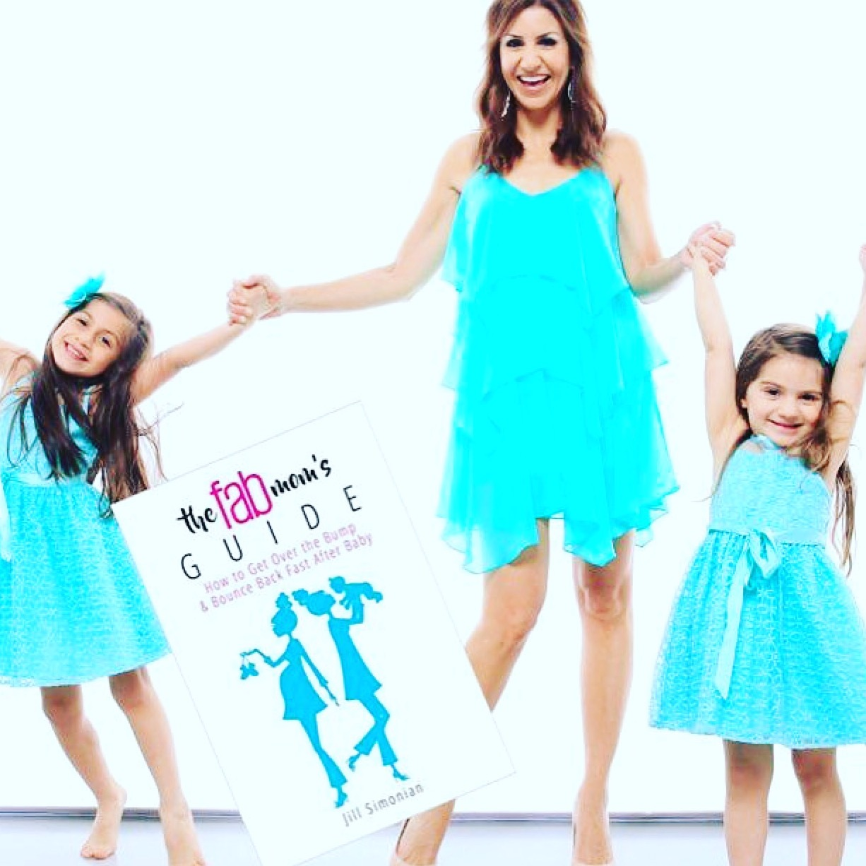 Jill Simonian, author of The FAB Mom's Guide book, holds hands with her daughters.