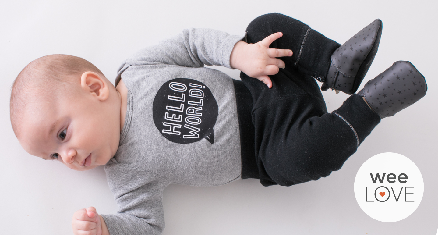 baby playing on his back, wearing baby nanya vegan baby shoes