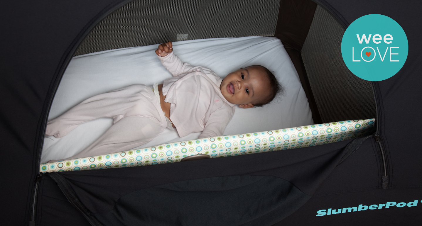 baby sleeping in a pack n play travel crib with a slumberpod over the crib, with a weelove sticker in the upper right-hand corner