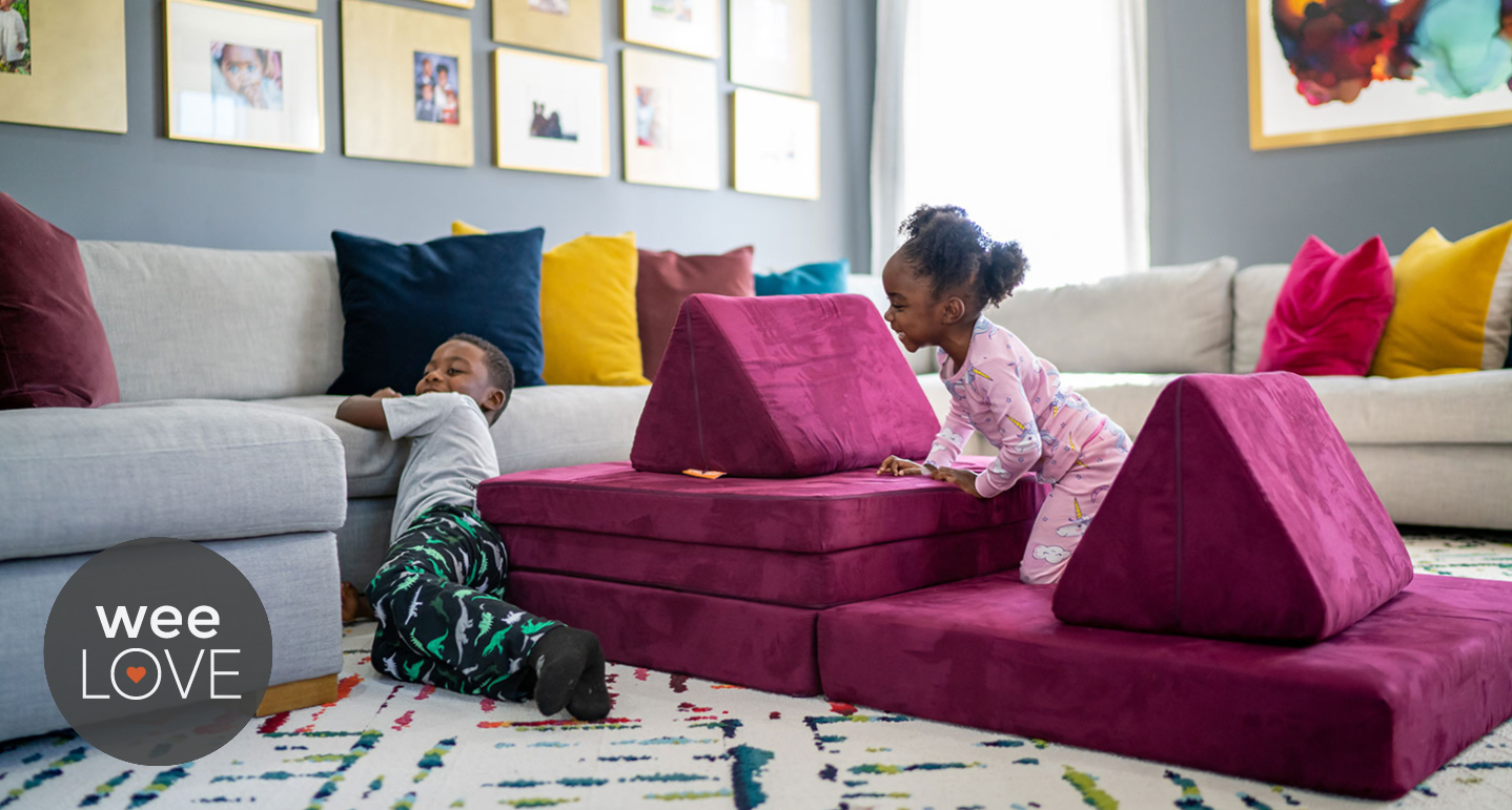 Two toddlers play on a magenta nugget couch that they have arranged on the floor of their living room like a pirate ship.