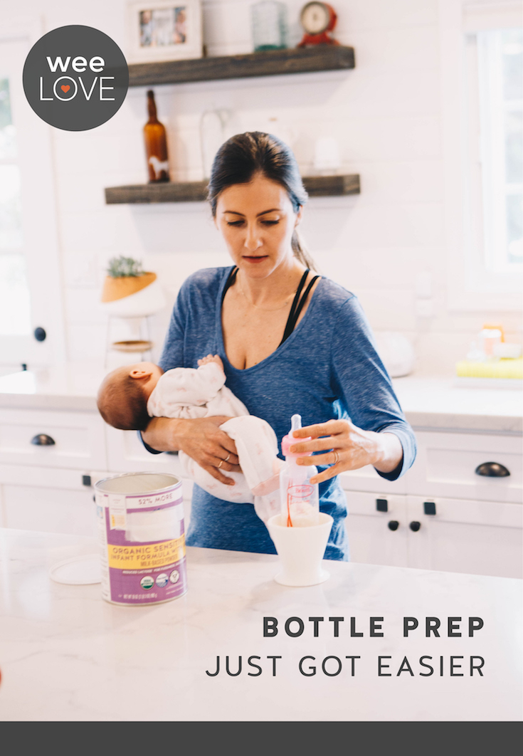 a white woman is holding a baby in one arm, and making a bottle one-handed using the bökee on kitchen countertop