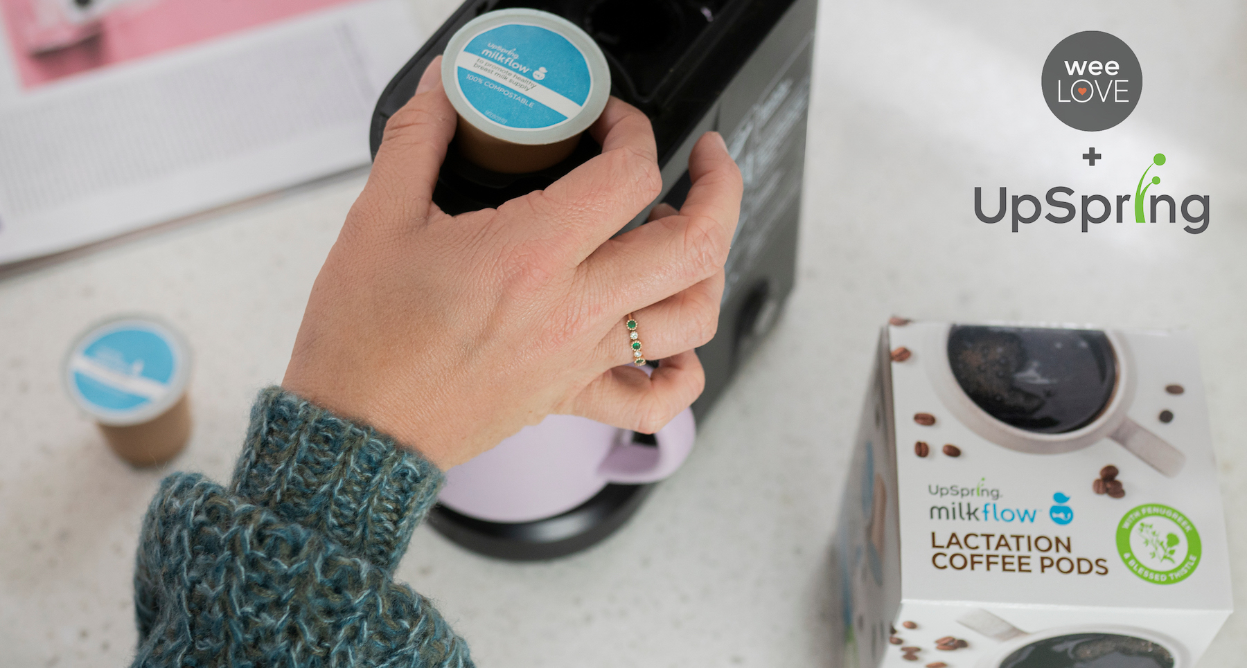 You can see a hand placing an UpSpring Milkflow Lactation Coffee Pod into a Keurig-style coffee machine. The machine is on a white counter, and a box of Milkflow Lactation Coffee Pods is laying nearby.