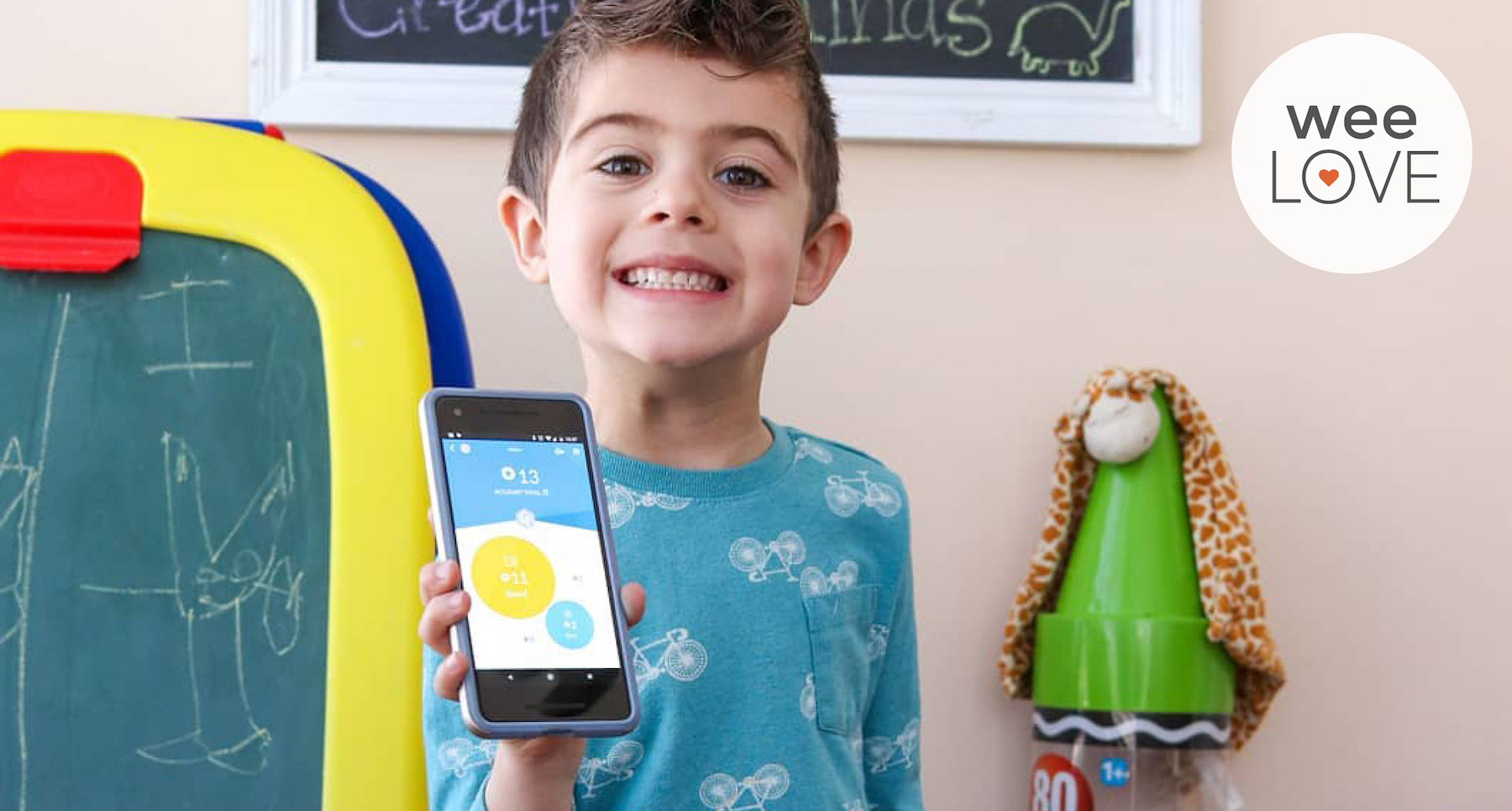 an image of a smiling young boy in a playroom, there is a chalkboard easel behind him, and he's holding a phone with the Rooster Money Allowance app on it.