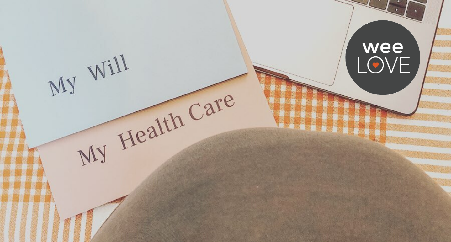"""an image is shot from overhead, showing a pregnant belly next to a computer screen and two folders from Trust & Will labeled """"my will"""" and """"my health care"""""""