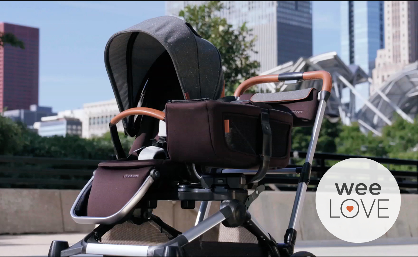 photo of the element convertible stroller from Contours outside near Millennium Park in Chicago. Shown with a forward-facing toddler seat and a tandem tote carry bag.