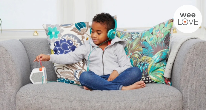 a young Black boy sits on a grey chair with comfy cushions, listening to his Yoto audio player with headphones